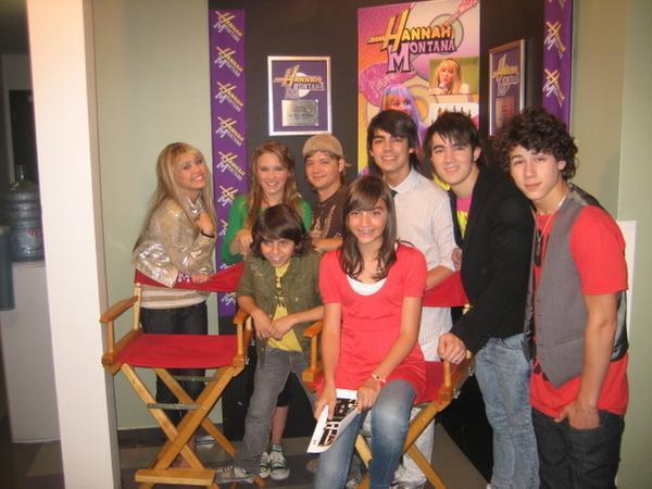 Emily Osment  segunda (de verde) al lado de Miley Cyrus junto a los Jonas Brothers